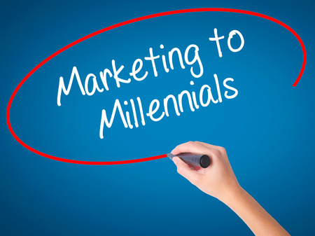 demografia: Mujeres mano escribiendo Marketing a los Millennials con marcador negro en la pantalla visual. Aislado en azul. Negocios, tecnología, concepto de internet. Foto de stock