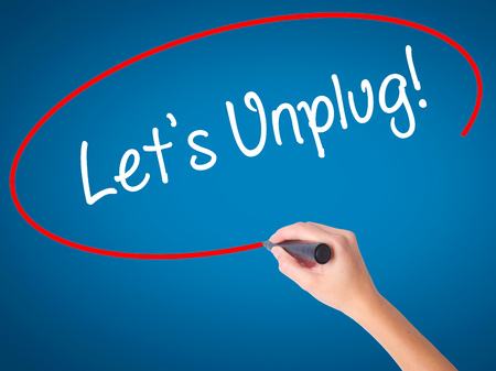 inaccessible: Women Hand writing Lets Unplug! with black marker on visual screen. Isolated on blue. Business, technology, internet concept. Stock Photo