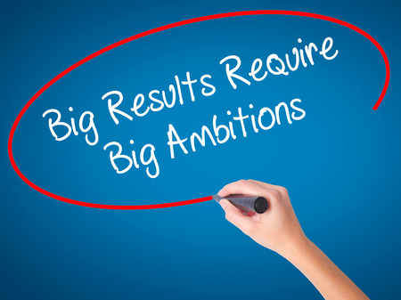 ambitions: Women Hand writing Big Results Require Big Ambitions with black marker on visual screen. Isolated on blue. Business, technology, internet concept. Stock Photo