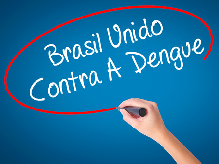 Women Hand writing Brasil Unido  Contra A Dengue (Brazil against Dengue in Portuguese) with black marker on visual screen. Isolated on blue. Business, technology, internet concept. Stock Photo Stock Photo