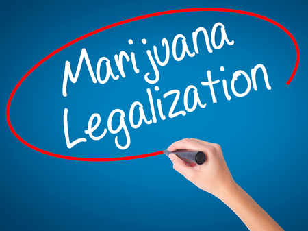 legislators: Women Hand writing Marijuana Legalization with black marker on visual screen. Isolated on blue. Live, technology, internet concept. Stock Photo