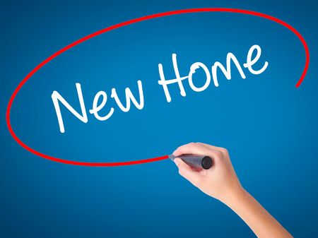 luxacion: Women Hand writing New Home  with black marker on visual screen. Isolated on blue. Business, technology, internet concept. Stock Photo