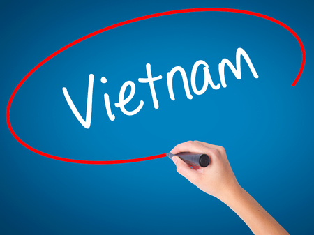 Women Hand writing Vietnam with black marker on visual screen. Isolated on blue. Business, technology, internet concept.