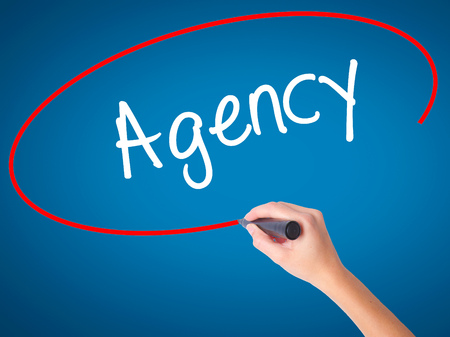stock agency: Women Hand writing Agency with black marker on visual screen. Isolated on blue. Business, technology, internet concept. Stock Photo