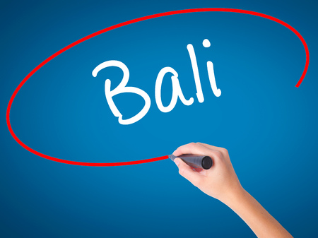 bali province: Women Hand writing Bali  with black marker on visual screen. Isolated on blue. Business, technology, internet concept. Stock Photo Stock Photo