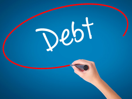Women Hand writing Debt with black marker on visual screen. Isolated on blue. Business, technology, internet concept.