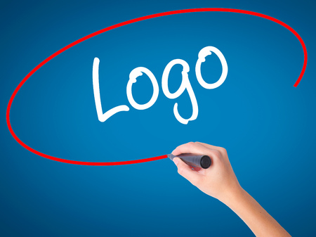 trademark: Women Hand writing Logo with black marker on visual screen. Isolated on blue. Business, technology, internet concept. Stock Photo