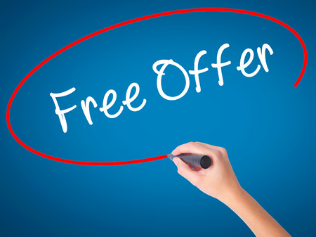Women Hand writing Free Offer  with black marker on visual screen. Isolated on blue. Business, technology, internet concept. Stock Photo Stock Photo