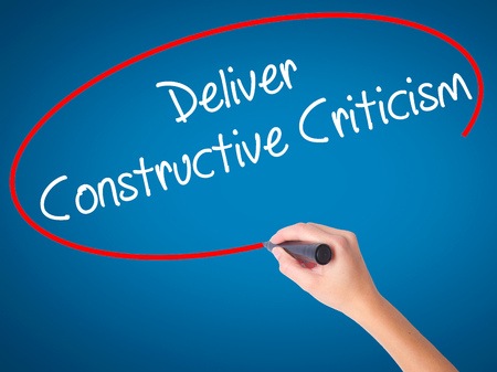 critical thinking: Women Hand writing Deliver Constructive Criticism with black marker on visual screen. Isolated on blue. Business, technology, internet concept. Stock Photo