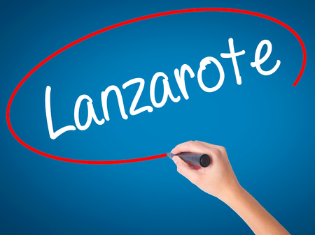 Women Hand writing Lanzarote with black marker on visual screen. Isolated on blue. Business, technology, internet concept. Stock Photo