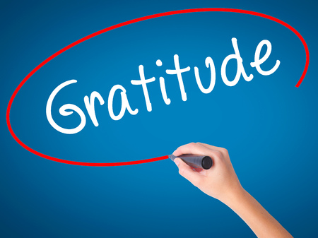 payer: Women Hand writing Gratitude with black marker on visual screen. Isolated on blue. Business, technology, internet concept. Stock Photo
