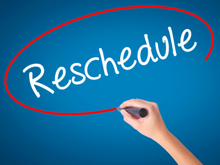 Women Hand writing Reschedule  with black marker on visual screen. Isolated on blue. Business, technology, internet concept. Stock Photo Stock Photo