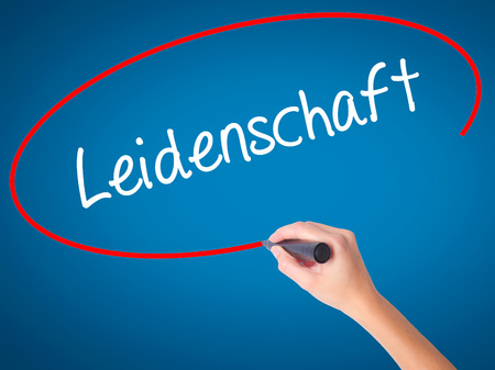 Women Hand writing Leidenschaft (Passion in German)  with black marker on visual screen. Isolated on blue. Business, technology, internet concept. Stock Photo Stock Photo