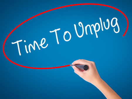 unplugging: Women Hand writing Time To Unplug with black marker on visual screen. Isolated on blue. Business, technology, internet concept. Stock Photo
