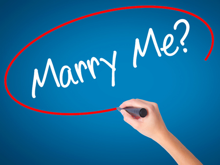 Women Hand writing Marry Me? with black marker on visual screen. Isolated on blue. Business, technology, internet concept. Stock  Photo Stock Photo