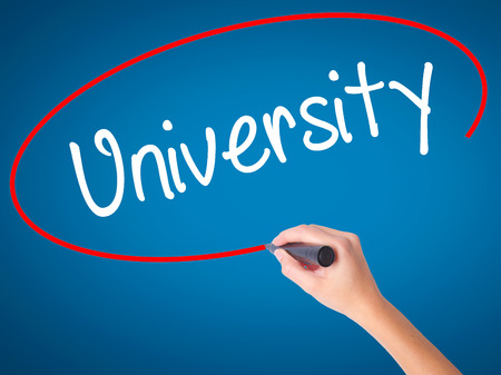 Women Hand writing University with black marker on visual screen. Isolated on blue. Business, technology, internet concept. Stock Photo Stock Photo