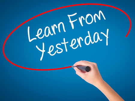 Women Hand writing Learn From Yesterday with black marker on visual screen. Isolated on blue. Business, technology, internet concept. Stock Photo