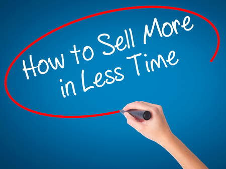 work less: Women Hand writing How to Sell More in Less Time with black marker on visual screen. Isolated on blue. Business, technology, internet concept. Stock Photo Stock Photo