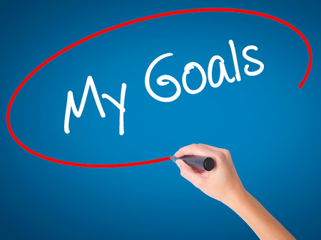 Women Hand writing  My Goals with black marker on visual screen. Isolated on blue. Business, technology, internet concept. Stock Photo Stock Photo