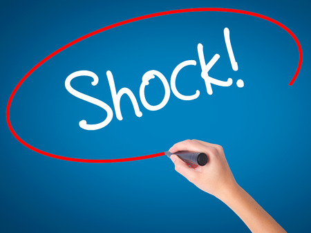 Women Hand writing Shock! with black marker on visual screen. Isolated on blue. Business, technology, internet concept. Stock Photo