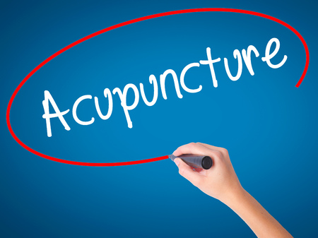 acupuncturist: Women Hand writing Acupuncture with black marker on visual screen. Isolated on blue. Business, technology, internet concept. Stock Photo