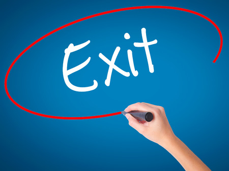 dissolve: Women Hand writing Exit with black marker on visual screen. Isolated on blue. Business, technology, internet concept. Stock Photo
