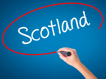 Women Hand writing Scotland with black marker on visual screen. Isolated on blue. Business, technology, internet concept. Stock  Photo Stock Photo