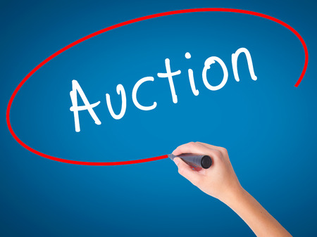 vend: Woman Hand writing Auction with black marker on visual screen. Isolated on white. Business, technology, internet concept. Stock Image