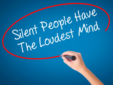 Women Hand writing Silent People Have The Loudest Mind with black marker on visual screen. Isolated on blue. Business, technology, internet concept. Stock Photo Stock Photo