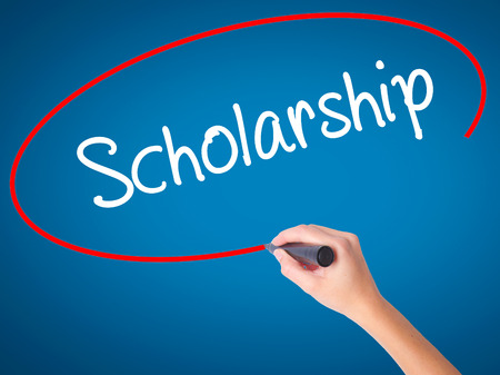 Women Hand writing Scholarship with black marker on visual screen. Isolated on blue. Business, technology, internet concept. Stock Photo Standard-Bild