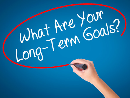Woman Hand writing What Are Your Long-Term Goals with black marker on visual screen. Isolated on white. Business, technology, internet concept. Stock Photo