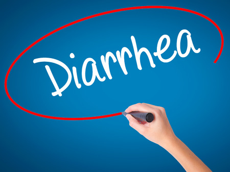 Women Hand writing  Diarrhea  with black marker on visual screen. Isolated on blue. Business, technology, internet concept. Stock Photo