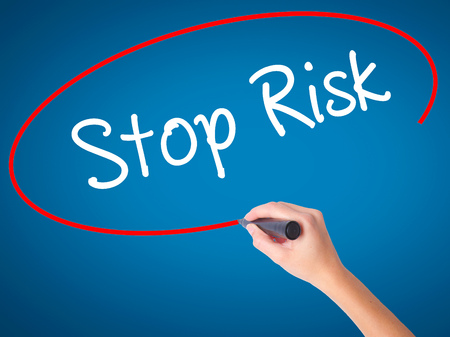reduce risk: Women Hand writing Stop Risk with black marker on visual screen. Isolated on blue. Business, technology, internet concept. Stock Photo