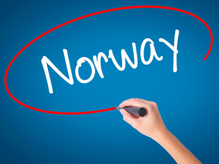 Women Hand writing Norway  with black marker on visual screen. Isolated on blue. Business, technology, internet concept. Stock Photo