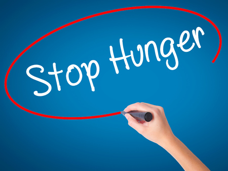 malnutrition: Women Hand writing  Stop Hunger with black marker on visual screen. Isolated on blue. Business, technology, internet concept. Stock Photo