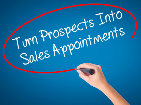Women Hand writing Turn Prospects Into Sales Appointments with black marker on visual screen. Isolated on blue. Business, technology, internet concept. Stock  Photo