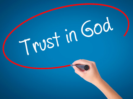 Women Hand writing Trust in God with black marker on visual screen. Isolated on blue. Business, technology, internet concept. Stock Photo
