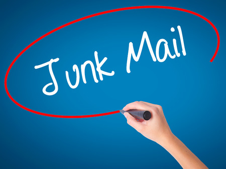 solicitors: Women Hand writing Junk Mail with black marker on visual screen. Isolated on blue. Business, technology, internet concept. Stock Photo