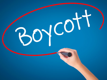 denying: Women Hand writing Boycott with black marker on visual screen. Isolated on blue. Business, technology, internet concept. Stock Photo Stock Photo