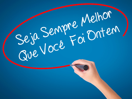 Women Hand writing Seja Sempre Melhor Que Voc??Â? Foi Ontem (Be Better Than You Were Yesterday in Portuguese) with black marker on visual screen. Isolated on blue. Business concept. Stock Photo Stock Photo