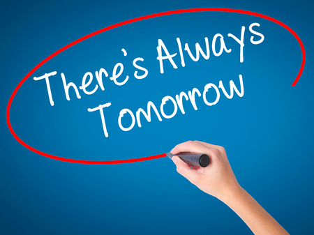 Women Hand writing Theres Always Tomorrow  with black marker on visual screen. Isolated on blue. Business, technology, internet concept. Stock Photo