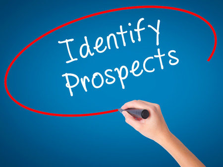 Women Hand writing Identify Prospects with black marker on visual screen. Isolated on blue. Business, technology, internet concept. Stock Photo