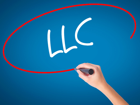 limited: Women Hand writing  LLC (Limited Liability Company)  with black marker on visual screen. Isolated on blue. Business, technology, internet concept. Stock Photo