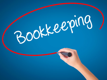 Women Hand writing Bookkeeping with black marker on visual screen. Isolated on blue. Business, technology, internet concept. Stock Photo Stock Photo