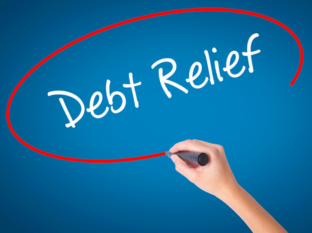 Women Hand writing Debt Relief with black marker on visual screen. Isolated on blue. Business, technology, internet concept. Stock Photo Stock Photo