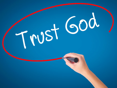 trust in god: Women Hand writing Trust God  with black marker on visual screen. Isolated on blue. Business, technology, internet concept. Stock Photo Stock Photo