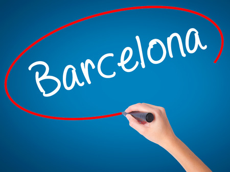 Women Hand writing Barcelona with black marker on visual screen. Isolated on blue. Business, technology, internet concept. Stock Photo Stock Photo