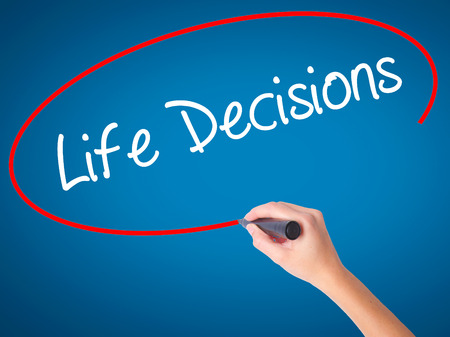 Women Hand writing Life Decisions with black marker on visual screen. Isolated on blue. Business, technology, internet concept. Stock Photo