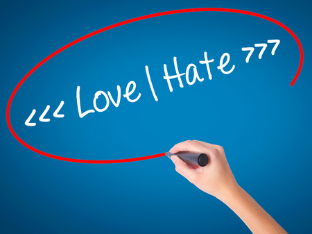 Women Hand writing Love - Hate  with black marker on visual screen. Isolated on blue. Business, technology, internet concept. Stock Photo Stock Photo