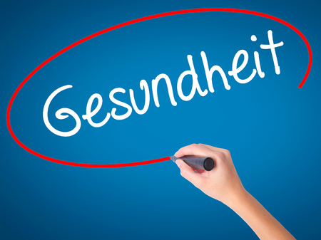 Women Hand writing Gesundheit (Health in German)  with black marker on visual screen. Isolated on blue. Business, technology, internet concept. Stock Photo
